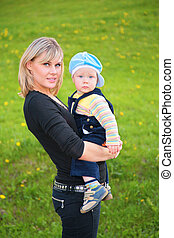 mother keeps child in her arms at meadow