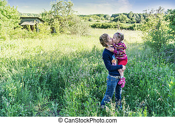 Mother kisses daughter in nature