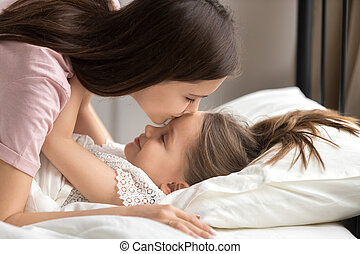 Mother kisses daughter puts to sleep in the afternoon nap