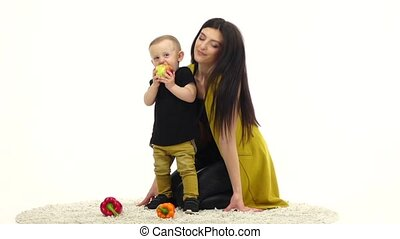 Mother kisses her baby, he laughs. White background. Slow...