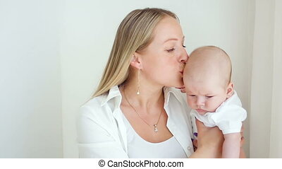 mother kisses her newborn son