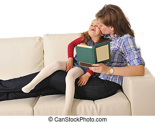 Mother kissing and telling fairy tale to cute little daughter
