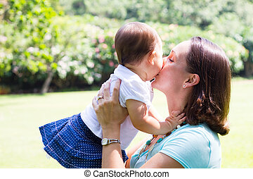 mother kissing baby daughter