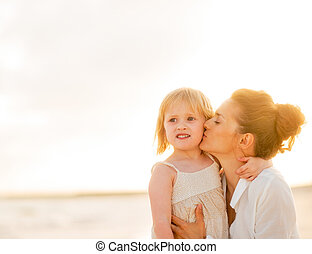 Mother kissing baby girl on beach at the evening