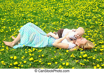 Mother Kissing Baby in Dandelion Field