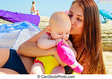 Mother kissing baby in swimsuit on beach