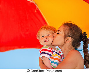Mother kissing baby on beach under umbrella