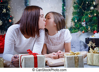 Mother kissing daughter on cheek at Christmas