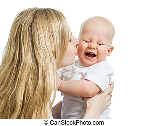 mother kissing her baby boy isolated on white