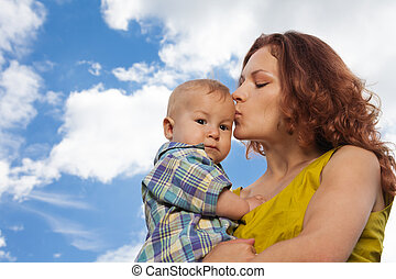 mother kissing her baby on cloudy background