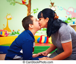 mother kissing her beloved son with disability in...