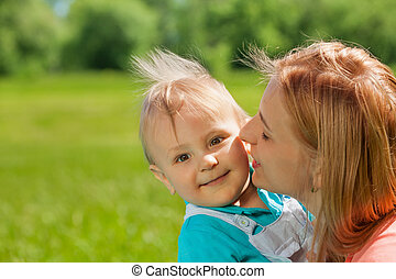 Mother kissing her child in cheek during summer