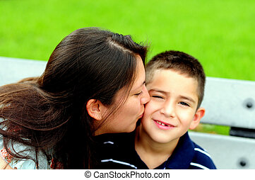 Mother kissing her child on the cheek
