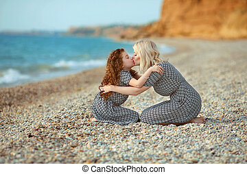 Mother kissing her daughter on the beach. outdoor family portrait. two same look person.