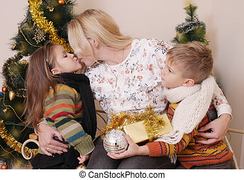 Mother kissing her two children