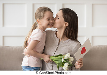 Mother kissing little daughter express gratitude for flowers and postcard