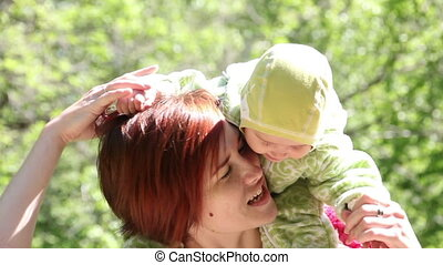 Mother kissing your baby in park