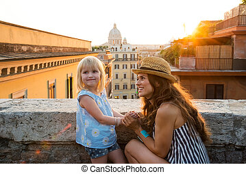 Mother kneeling by daughter above Rome at sunset - With...