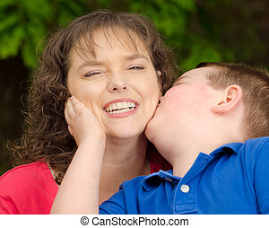 Mother laughing at kiss from son