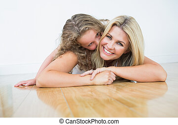 Mother laying with her daughter on the floor