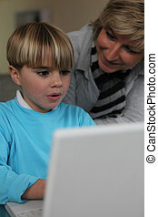 mother learning her little boy how to write on a laptop