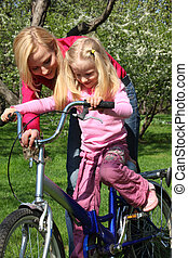 Mother learns  daughter to go by  bicycle in  spring garden