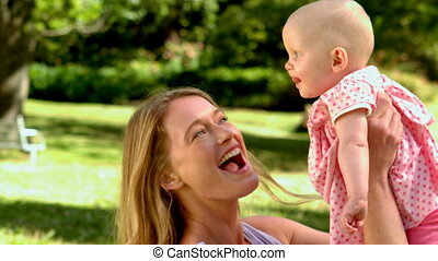 Mother lifting her baby girl in th