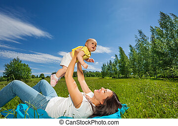 Mother lifting her baby up with straight arms