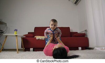 Mother lifting newborn son in the air at home - Mother lying...