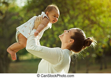 Beautiful woman lifts high her adorable baby up mid air and looks at her smiling. Happy parent spending time playing with daughter in park at sunset. Medium shot