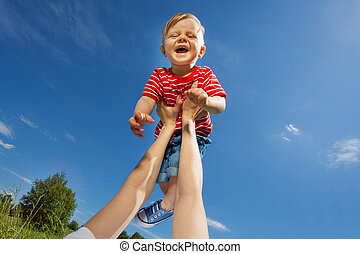 Mother lifts laughing son up with straight arms