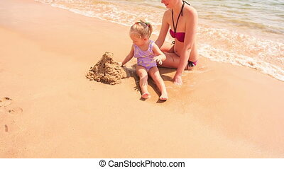 Mother Little Daughter Build Sand Castle on Beach of Azure Sea
