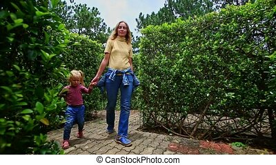Mother Little Girl Walk between Long Hedge Labyrinth in Park...