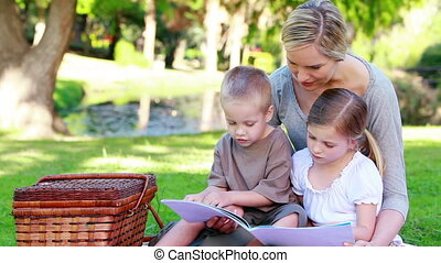 Mother looking a picture book with her children in a park