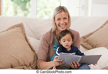 Mother looking at a book with her s