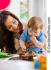 Mother Looking At Baby Boy Eating Cupcake