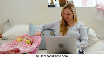 Mother looking at baby while using laptop 4k
