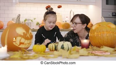 Mother looking at daughter painting pumpkin - Woman in...