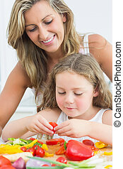Mother looking at daughter preparing vegetables
