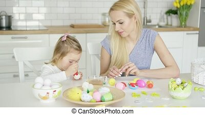 Mother looking at girl coloring eggs