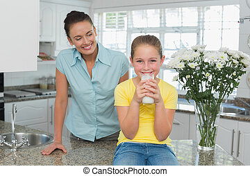 Mother looking at girl drinking milk in kitchen
