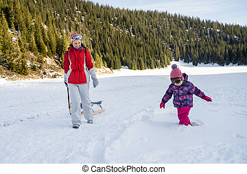 Mother Looking At Her Daughter Playing In Snow