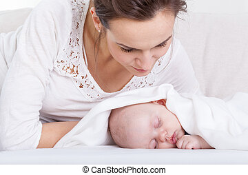 Mother looking at her sleeping baby