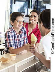 Mother Looking At Son Receiving Ice Cream From Waiter