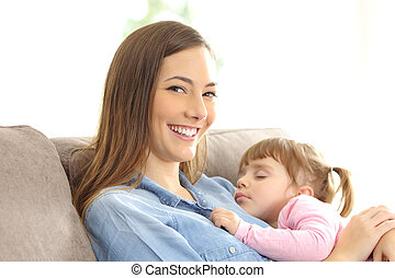 Mother looking at you with her daughter sleeping