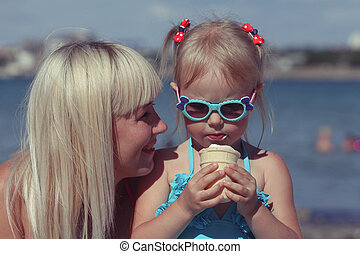 Mother looks at the daughter eating ice cream