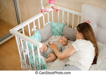 Mother lulling cute little newborn baby girl in bed