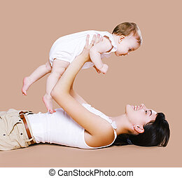 Mother lying and having fun with baby