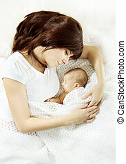 Mother lying down and embracing sleeping newborn baby....