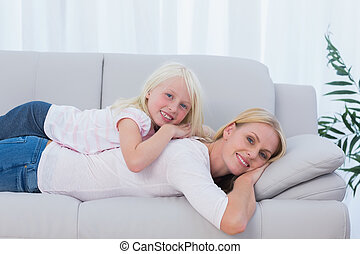 Mother lying on couch with her daughter on her back